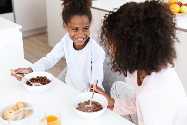 Afro-amerikaanse vrouw en haar dochtertje ontbijten en cornflakes eten in de keuken