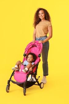 Afro-amerikaanse vrouw en haar schattige baby in kinderwagen