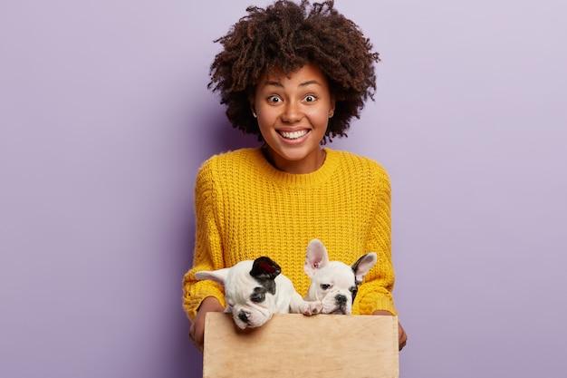 Afro-amerikaanse vrouw, gekleed in gele trui met puppy's