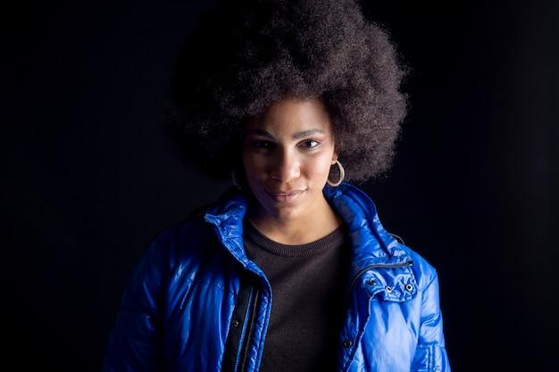 Afro-amerikaanse vrouw, gemengd ras, poseren op een donkere achtergrond, stedelijke kleding, modern mooi en glimlachend