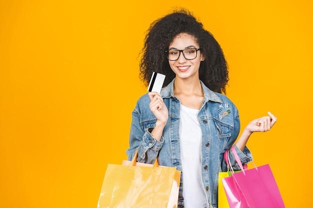 Afro-amerikaanse vrouw glimlachend en blij met kleurrijke boodschappentassen en creditcard