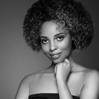 Afro-amerikaanse vrouw haar huid schoonheid. studio opname. monochroom. grijs. zwart en wit.
