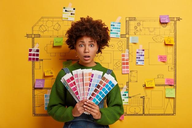 Afro-amerikaanse vrouw houdt kleurstalen voor nieuw appartement