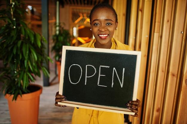 Afro-amerikaanse vrouw houdt open welkomstbord in moderne café-koffieshop klaar voor service, restaurant, winkel, eigenaar van een klein bedrijf. Premium Foto