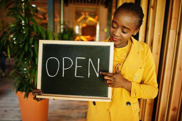 Afro-amerikaanse vrouw houdt open welkomstbord in moderne café-koffieshop klaar voor service, restaurant, winkel, eigenaar van een klein bedrijf.