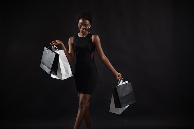 Afro-amerikaanse vrouw houdt zwarte boodschappentassen vast. verkoop en kortingen op markt en black friday-concept.