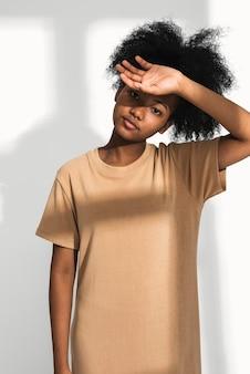 Afro-amerikaanse vrouw in bruine t-shirtjurk voor kledingshoot