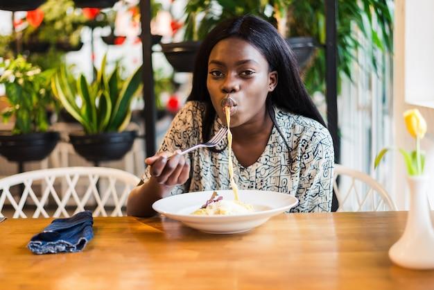 Afro-amerikaanse vrouw in café eet spaghetti pasta