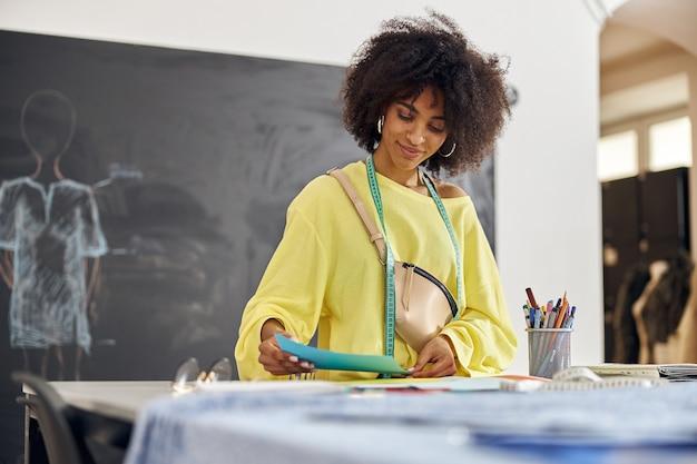 Afro-amerikaanse vrouw in losse gele trui met meetlint