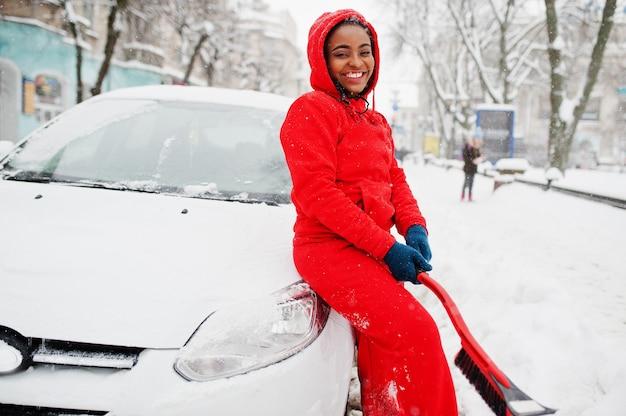 Afro-amerikaanse vrouw in rode hoodie schone auto uit sneeuw in winterdag.