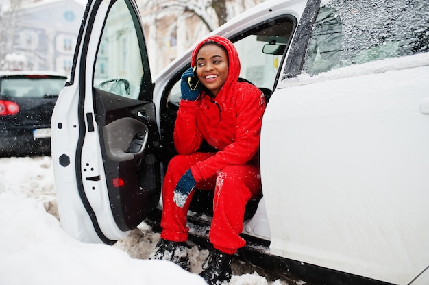 Afro-amerikaanse vrouw in rode hoodie zit in auto op besneeuwde winterdag met mobiele telefoon.