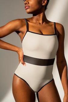 Afro-amerikaanse vrouw in wit badpak uit één stuk met zwarte streep strandmode