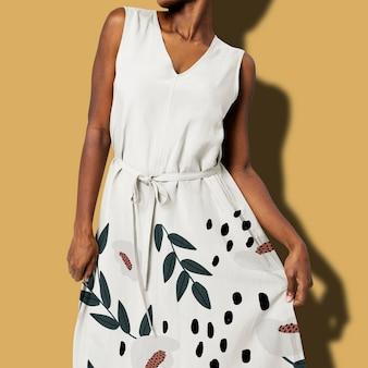 Afro-amerikaanse vrouw in witte bloemenjurk met riem voor damesmodeshoot