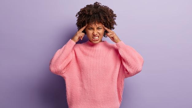 Afro-amerikaanse vrouw lijdt aan migraine, raakt slapen aan, heeft pijnstillers nodig, klemt tanden, kan de pijn niet vasthouden