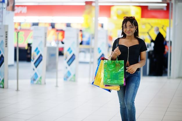 Afro-amerikaanse vrouw lopen met boodschappentassen in winkelcentrum