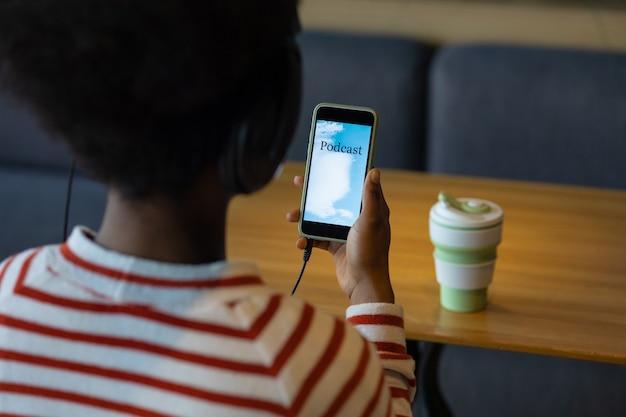 Afro-amerikaanse vrouw luistert naar podcast vanaf haar smartphone