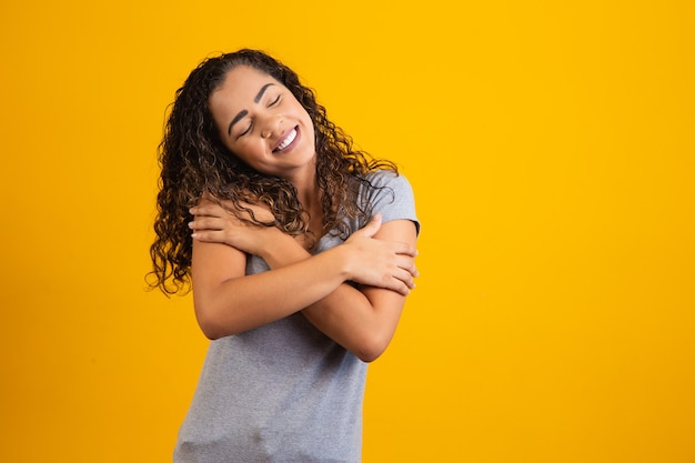 Afro-amerikaanse vrouw met afro-haar, gekleed in een casual t-shirt, zichzelf gelukkig en positief omhelzend, zelfverzekerd glimlachend. zelfliefde en zelfzorg