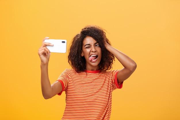 Afro-amerikaanse vrouw met afro kapsel in t-shirt selfie te nemen en tong uitsteekt