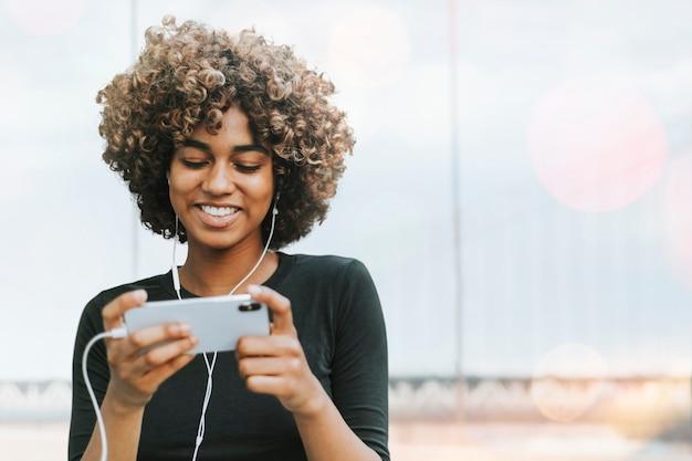 Afro-amerikaanse vrouw met geremixte media op smartphone