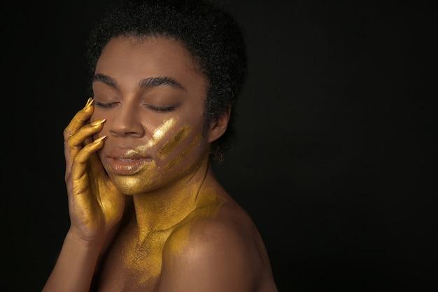 Afro-amerikaanse vrouw met gouden verf op haar lichaam