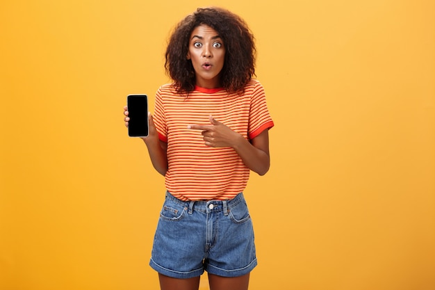 Afro-amerikaanse vrouw met krullend haar wijzend op mobiel met verbaasde expressie over oranje muur
