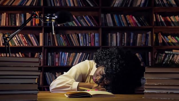 Afro-amerikaanse vrouw moe van het voorbereiden op tests, slaapt in de buurt van open papieren notitieboekje en stapel boeken op tafel tegen close-up van boekenplanken