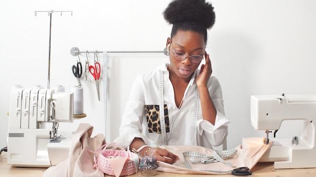 Afro-amerikaanse vrouw naaister, modeontwerper luisteren naar muziek via een koptelefoon tijdens het werken aan stof in de studio workshop