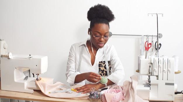 Afro-amerikaanse vrouw naait kleding in haar favoriete studio, werkplaats