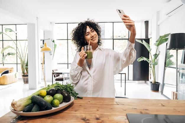Afro-amerikaanse vrouw neemt selfie en drinkt thuis groen sap gezonde levensstijl ruimte kopiëren