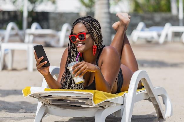 Afro-amerikaanse vrouw op het strand liggend op een ligstoel met behulp van telefoon en een verfrissend drankje drinken. vrolijke volwassen vrouw genieten van een zomerdag op het strand.