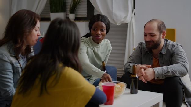 Afro-amerikaanse vrouw praat met vrienden die genieten van tijd samen doorbrengen