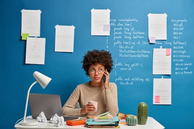 Afro-amerikaanse vrouw praat op mobiele telefoon op de werkplek, chats met vriend tijdens koffiepauze, afstandsproblemen op te lossen
