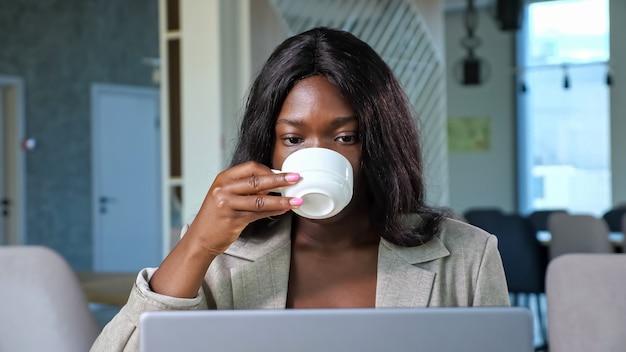 Afro-amerikaanse vrouw praat op videochat via laptop in café