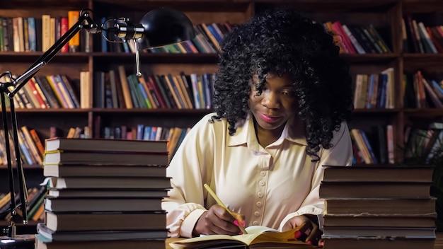 Afro-amerikaanse vrouw schrijft in notitieblok in openbare bibliotheek