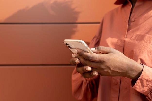 Afro-amerikaanse vrouw sms't iemand op haar smartphone