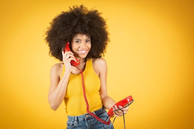 Afro-amerikaanse vrouw van gemengd ras met afro haar praten over de kabeltelefoon, gele achtergrond