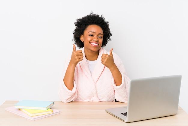 Afro-amerikaanse vrouw van middelbare leeftijd die thuis geïsoleerd werkt en beide duimen opheft, glimlachend en zelfverzekerd.