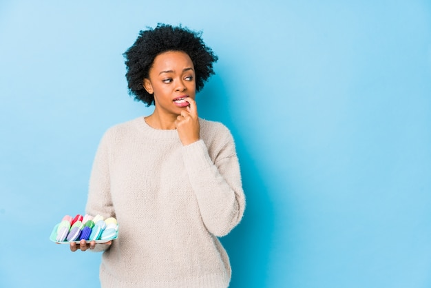 Afro-amerikaanse vrouw van middelbare leeftijd eten bitterkoekjes geïsoleerd ontspannen denken aan iets kijken naar een kopie ruimte.