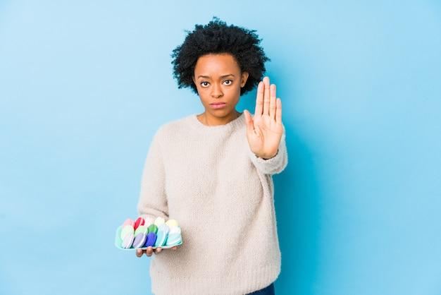 Afro-amerikaanse vrouw van middelbare leeftijd eten bitterkoekjes geïsoleerd staande met uitgestrekte hand weergegeven: stopbord, waardoor u.