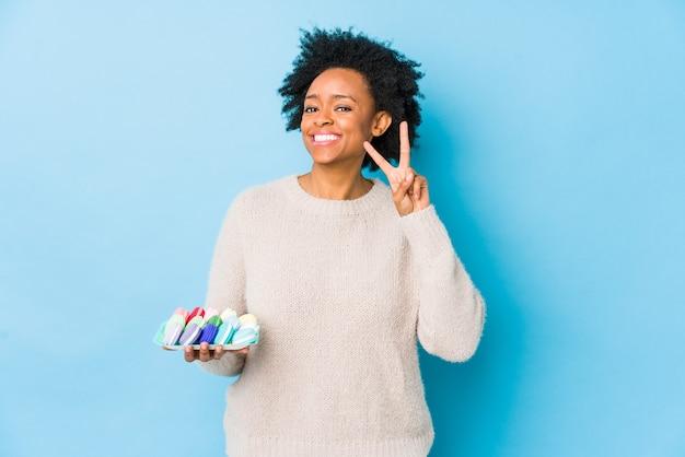 Afro-amerikaanse vrouw van middelbare leeftijd eten bitterkoekjes geïsoleerd weergegeven: overwinningsteken en breed glimlachend.