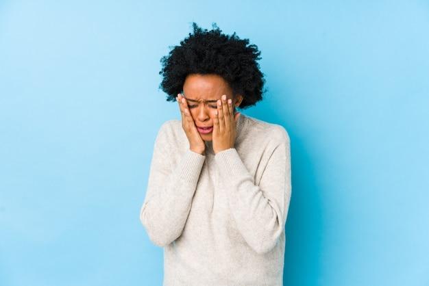 Afro-amerikaanse vrouw van middelbare leeftijd op een blauw geïsoleerd troosteloos janken en huilen.