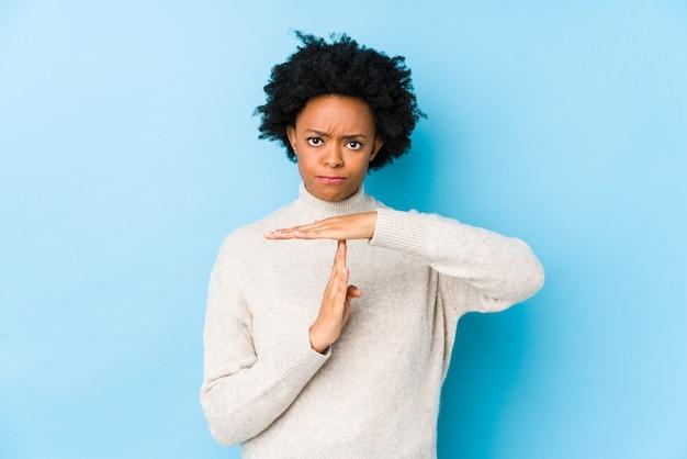 Afro-amerikaanse vrouw van middelbare leeftijd tegen een blauw geïsoleerd oppervlak met een time-outgebaar.