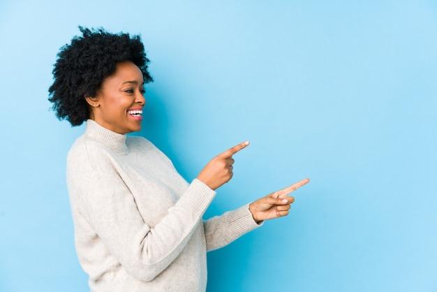 Afro-amerikaanse vrouw van middelbare leeftijd tegen een blauwe geïsoleerde opgewonden wijzend met wijsvingers weg.