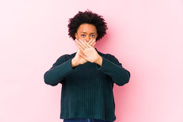 Afro-amerikaanse vrouw van middelbare leeftijd tegen een roze geïsoleerd die een ontkenningsgebaar doet