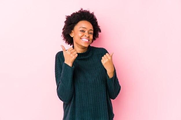 Afro-amerikaanse vrouw van middelbare leeftijd tegen een roze geïsoleerde muur die beide duimen opheft, glimlachend en zelfverzekerd.