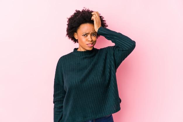 Afro-amerikaanse vrouw van middelbare leeftijd tegen een roze muur geïsoleerd geschokt, heeft ze belangrijke vergadering onthouden.