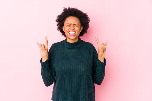 Afro-amerikaanse vrouw van middelbare leeftijd tegen een roze muur geïsoleerd tonen rock gebaar met vingers