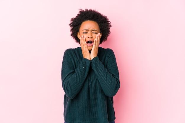 Afro-amerikaanse vrouw van middelbare leeftijd tegen een roze muur geïsoleerd troosteloos janken en huilen.