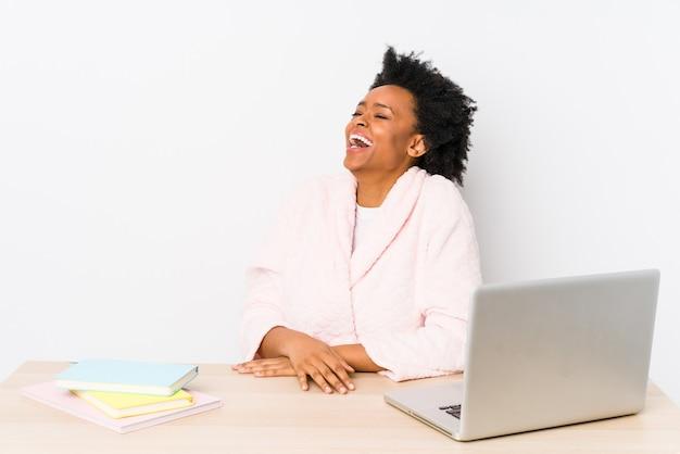 Afro-amerikaanse vrouw van middelbare leeftijd thuis werken geïsoleerd ontspannen en gelukkig lachen, nek gestrekt tanden tonen.