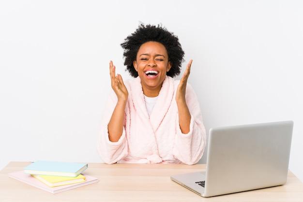 Afro-amerikaanse vrouw van middelbare leeftijd thuis werken geïsoleerd vrolijk lachen veel.